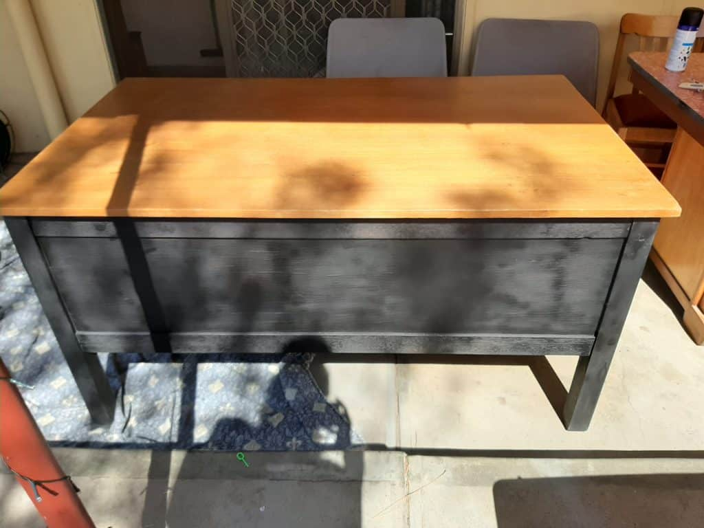 A wooden desk spray painted black with a wooden desk top.