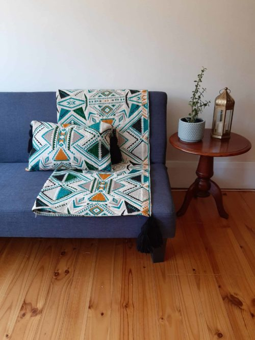 Plumbago aztec range pillows. Throw and pillow on sofa.