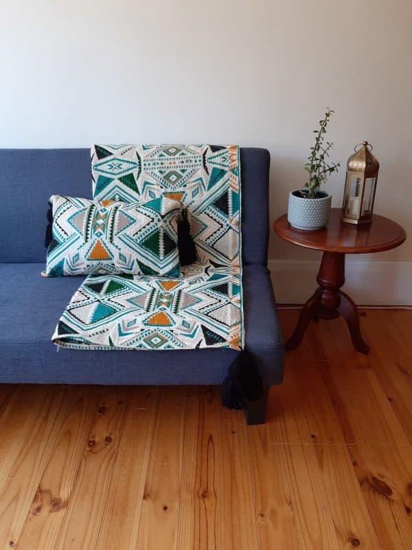 Plumbago aztec range pillows. Throw and pillow on sofa.