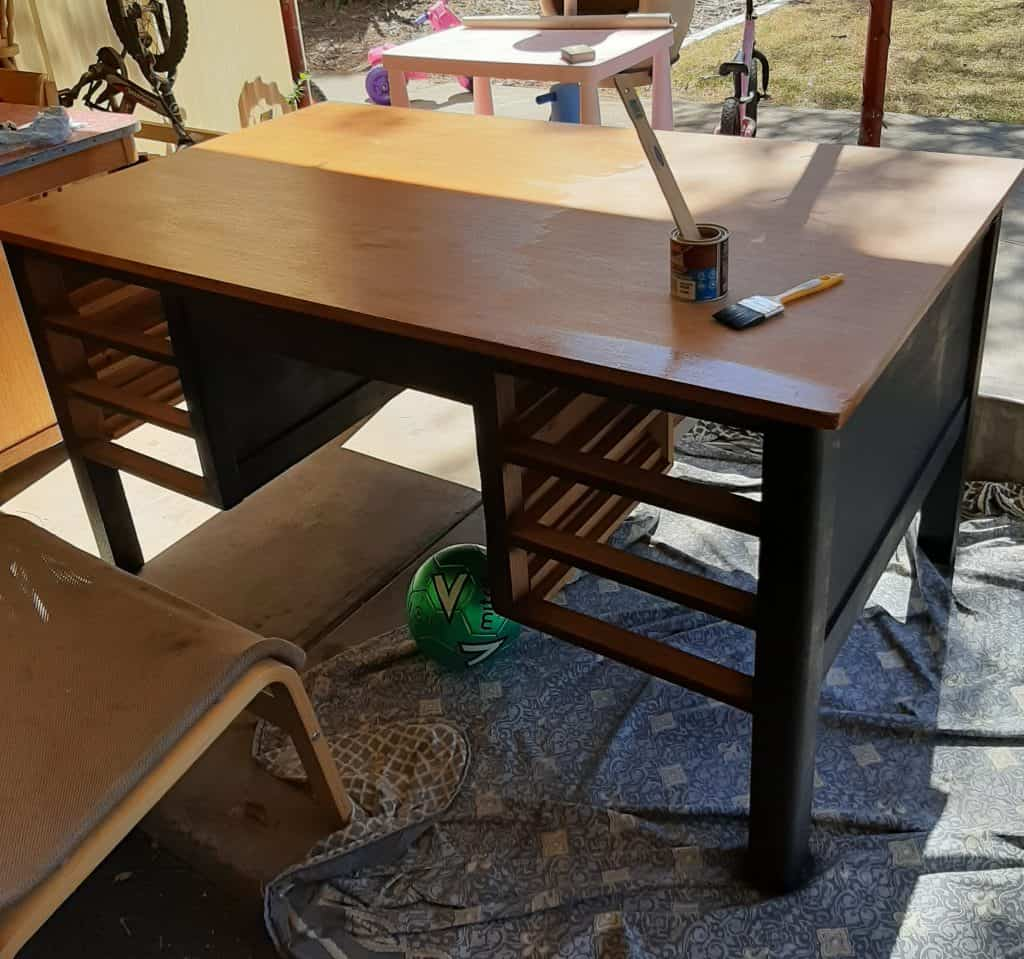 A photo of a desk prepped and being varnished.