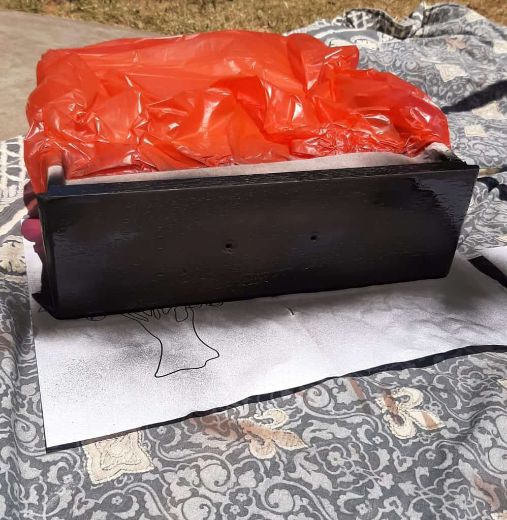 Photo of drawer masking taped and covered in a bin bag ready for spray painting.