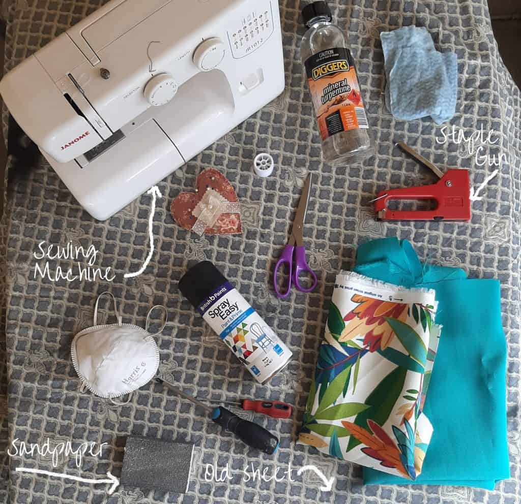 Photo of materials used during chair upcycle including staple gun, fabric, sewing machine, spray paint and screwdrivers.