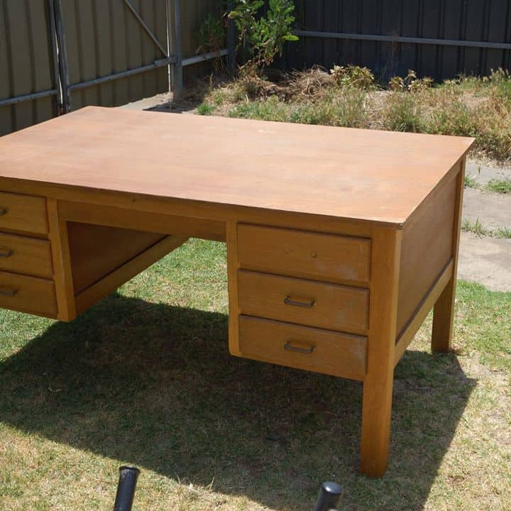 Old wooden desk with missing handle and scratched desk top