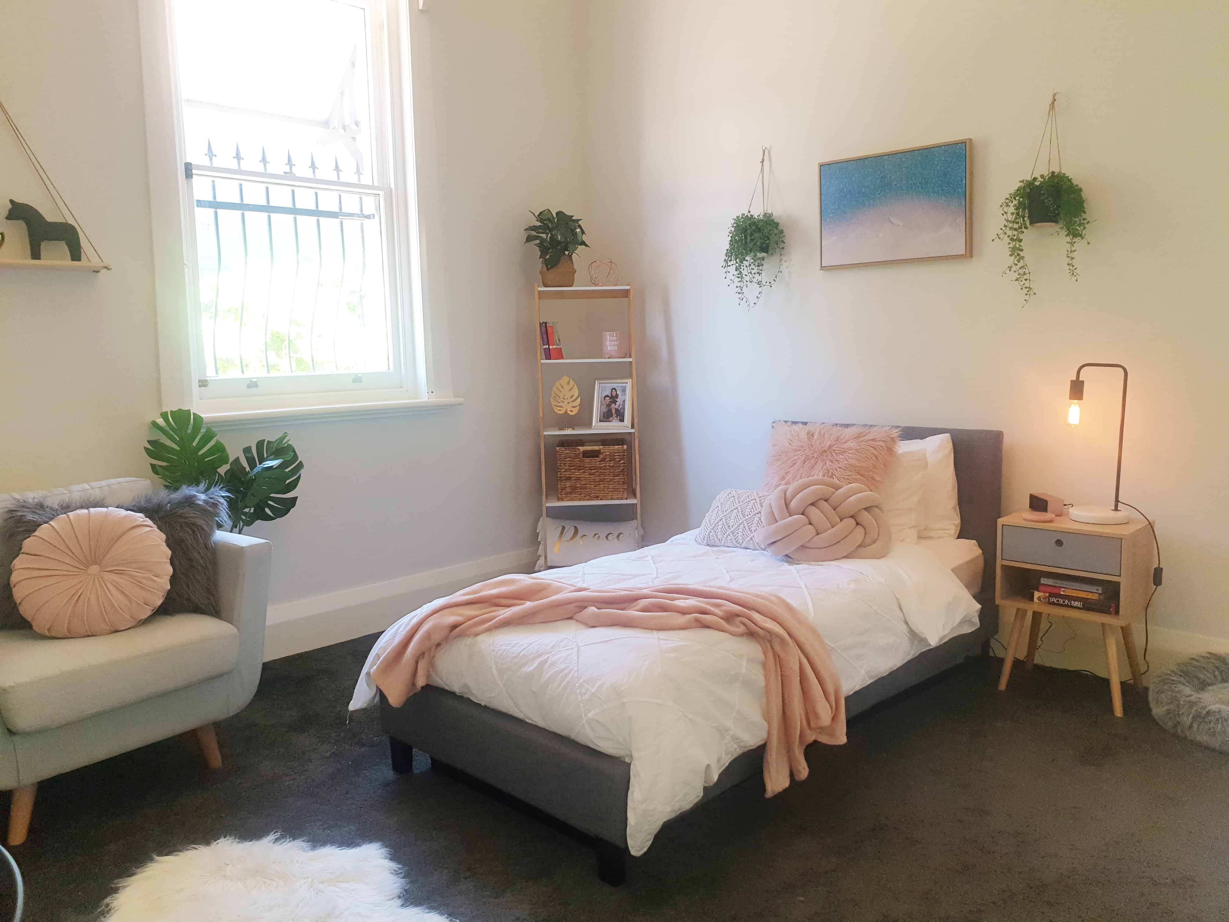 DIY bedroom makeover - whole room view of bed, bookshelf and chair. Hanging plants and fluffy rug.