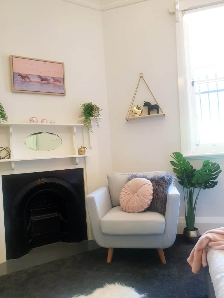 DIY Bedroom Makeover - reading corner with stylish armchair, hanging wall shelf and fireplace