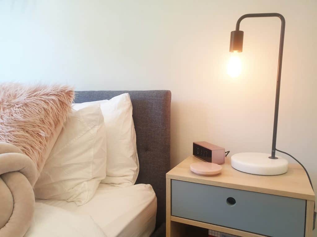 DIY Bedroom makeover - close up of bedside table with lamp and clock.