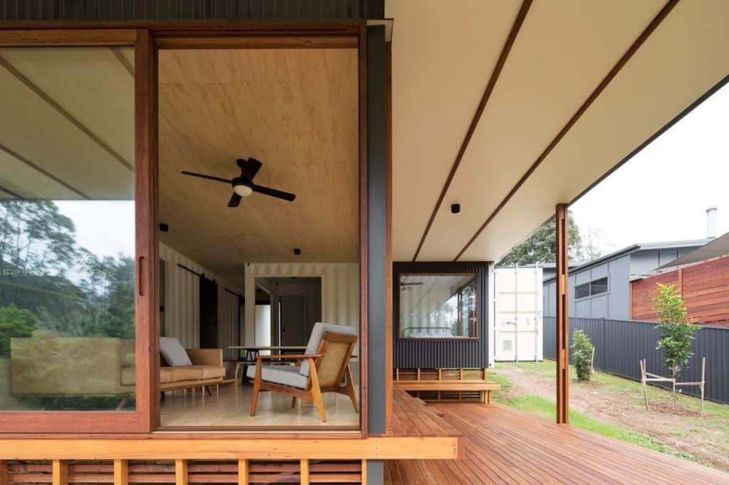 South Coast Container House living room opens up to deck area. Steel columns visible.