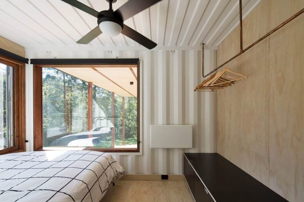 South coast container home bedroom with exposed metal sheet walls painted glossy white