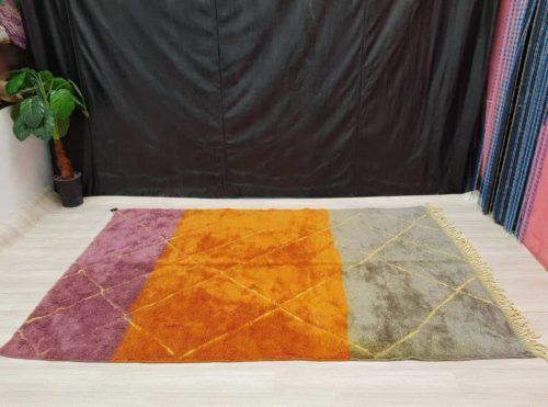 Adilah Purple Orange Rug laying on floor