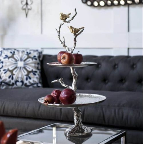 Bird and tree cakestand on display on table with apples on both levels.