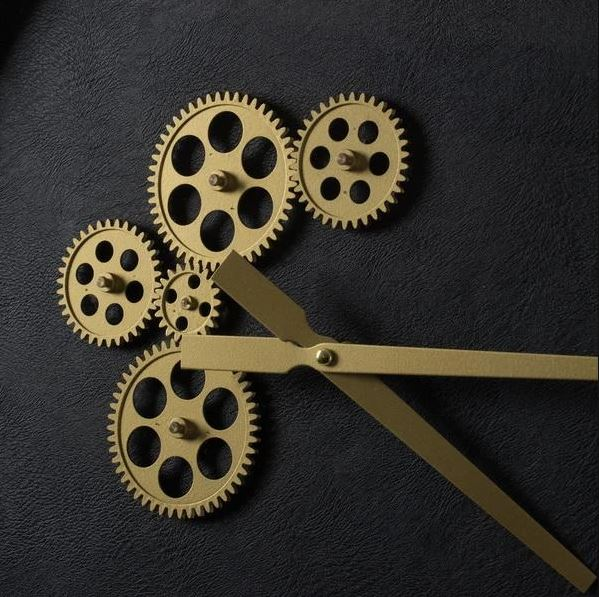 Black and gold wall clock with exposed mechanics close up of exposed gold mechanics detail