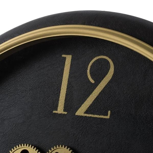 Black and gold wall clock with exposed mechanics close up of edge detail