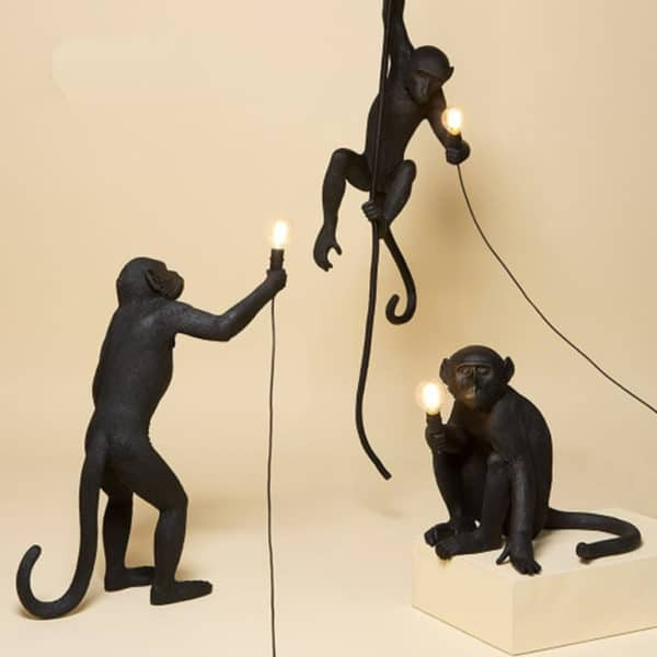 Monkey Lamps three, one sitting, one standing, one hanging in black