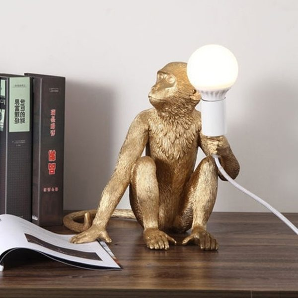 Monkey Lamp sitting in gold. Monkey reading book.