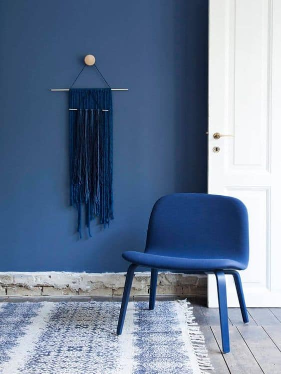 A Pantone color of 2020 classic blue chair and painted blue wall.
