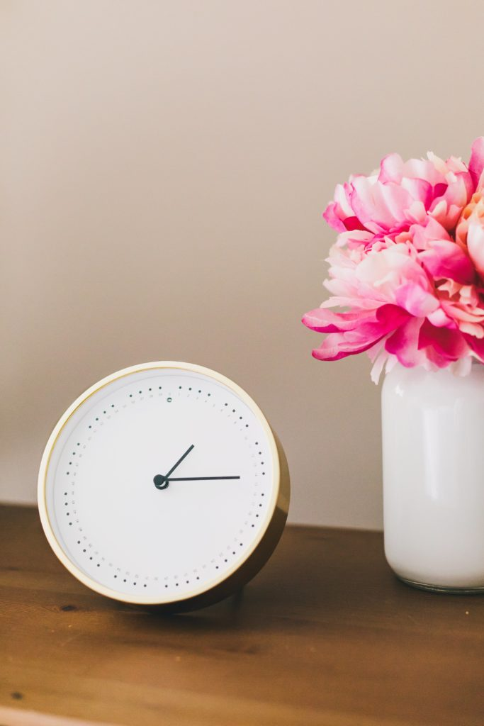 Minimalist living decor clock and flowers on table