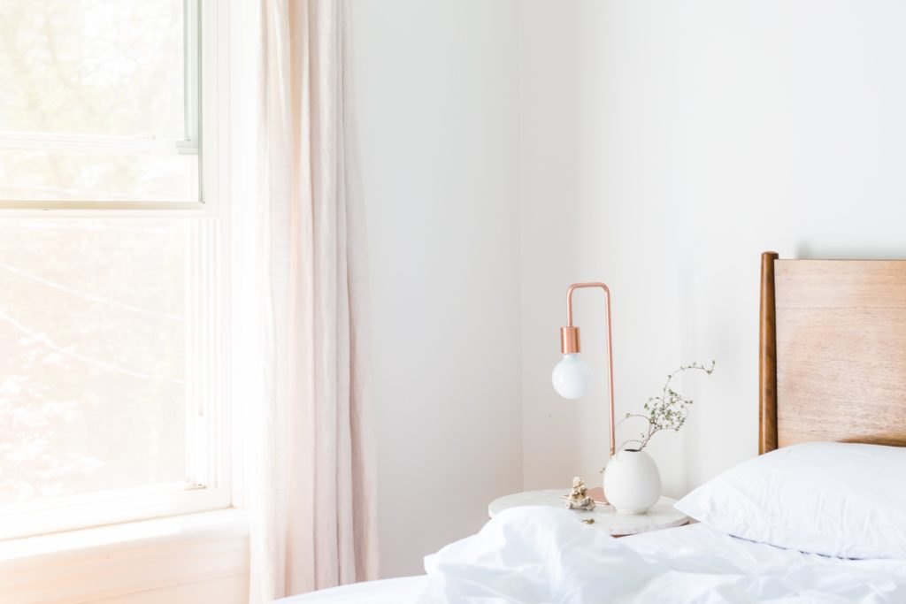 Calming bedroom with white walls and carefully selected decor items Gold lamp and flower in vase.