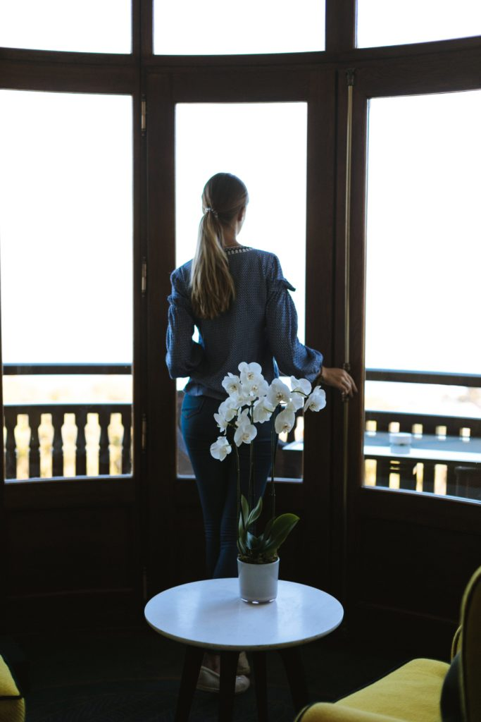 Minimalist living - giving yourself more time to spend on relationships. Woman looking out of window. Flowers on table in foreground.