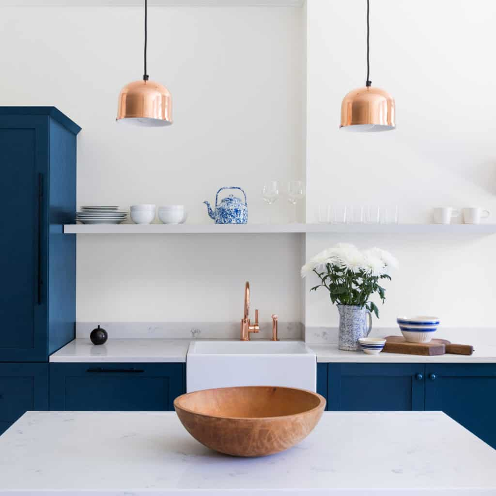 Pantone's Colour of the Year 2020 Classic Blue kitchen cupboards. White walls and copper accessories.