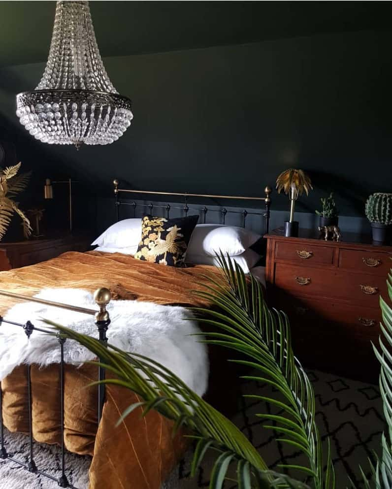 Dark decor trend featuring dark walls and ceiling mixed with soft gold velvet, plants and a chandelier for added glamour