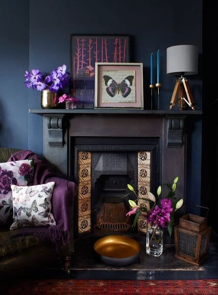 Dark living room featuring Victorian fireplace and hints of purple and metallics.