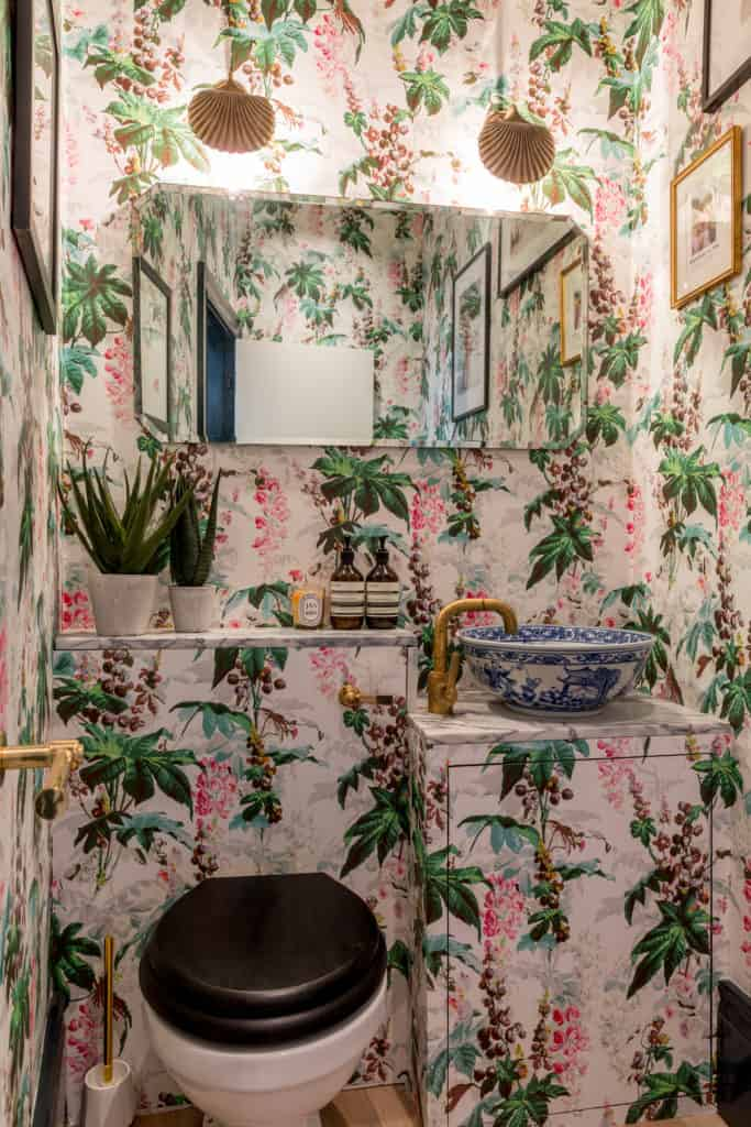 Maximalist powder room from Barlow & Barlow featuring floral wallpaper, porcelain sink and gold hardware