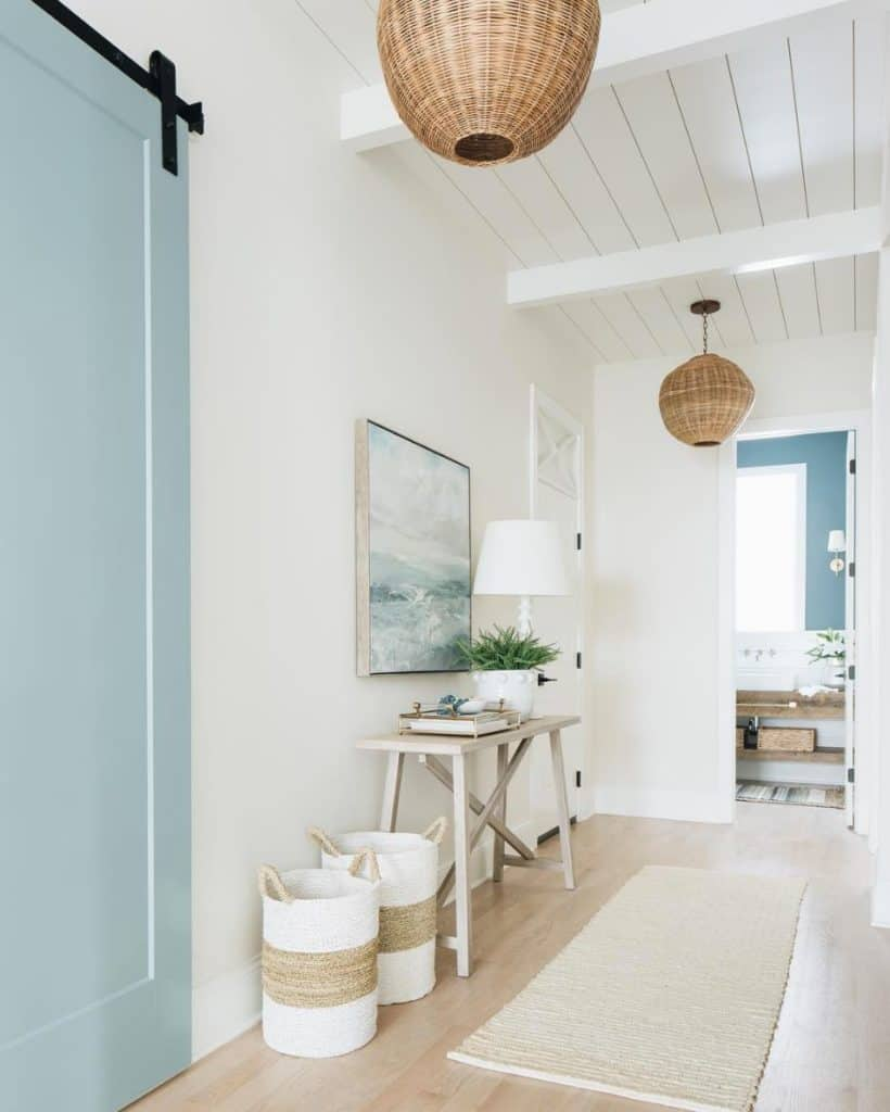 Coastal Entry featuring light timber floor, shiplap ceiling, wicker lampshades and coastal artwork