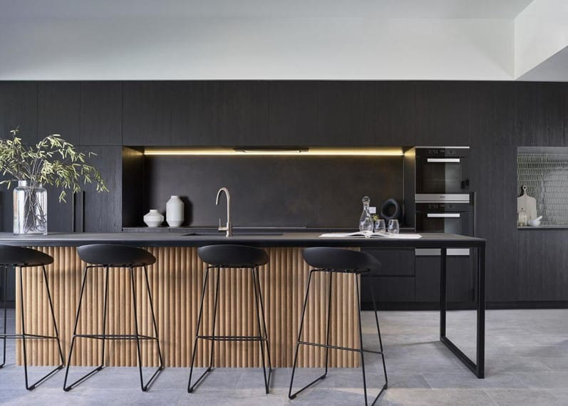 Dark decor trend featuring black kitchen including feature lighting and wooden detailing to soften the darkness