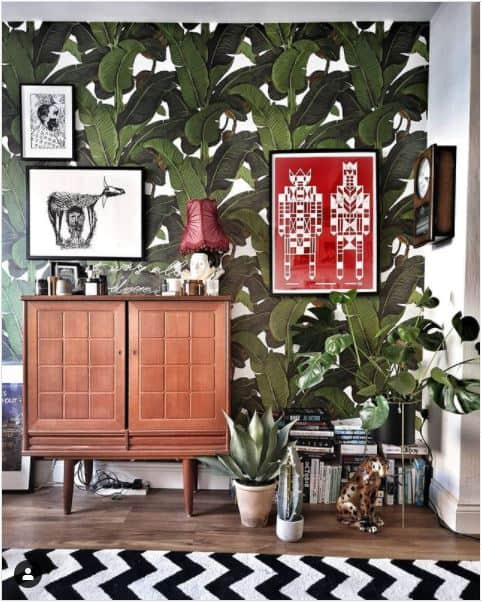70s wallpaper revival. Living room with bold tropical leaf print wallpaper.