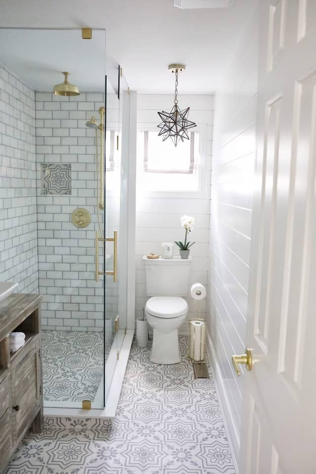 After bathroom renovation by Simply Beautiful Eating via Home Bunch. Featuring light and bright bathroom with beautiful tiles and gold fixtures.