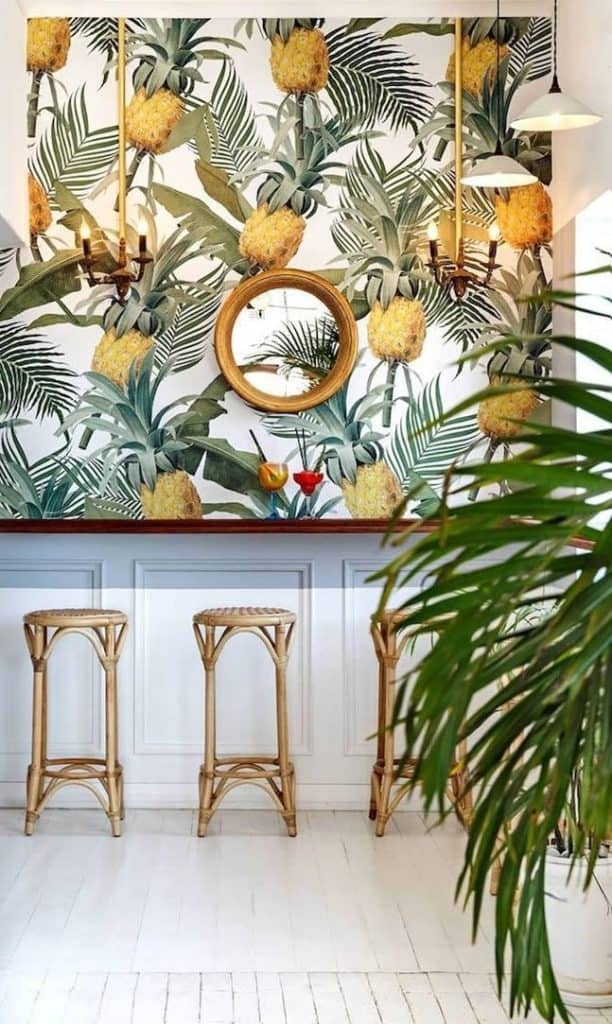 Travel inspired interior design reminding us of exotic places. Palms, rattan furniture, tropical patterns, lemon yellow.