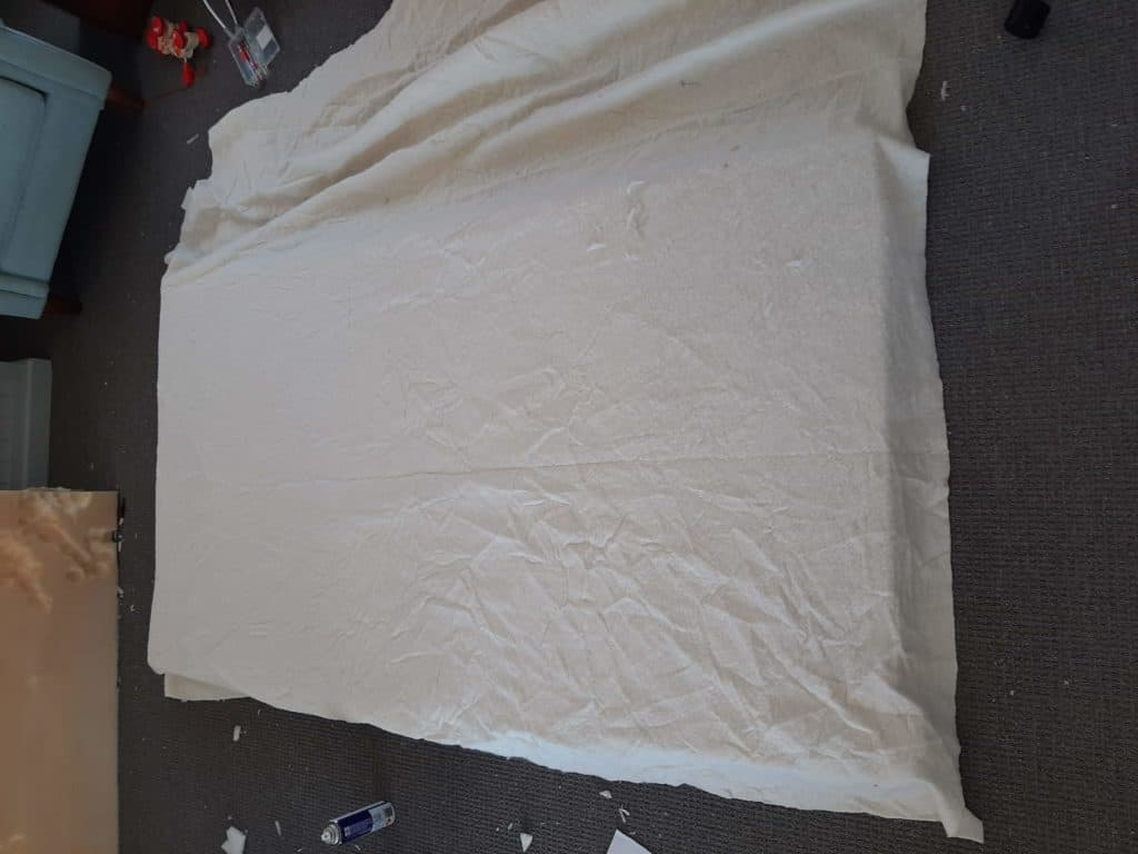 DIY upholstered headboard in progress. Board and foam covered in wadding.