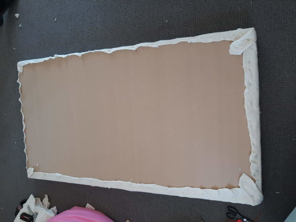 DIY upholstered headboard in progress. Wadding stapled to board.