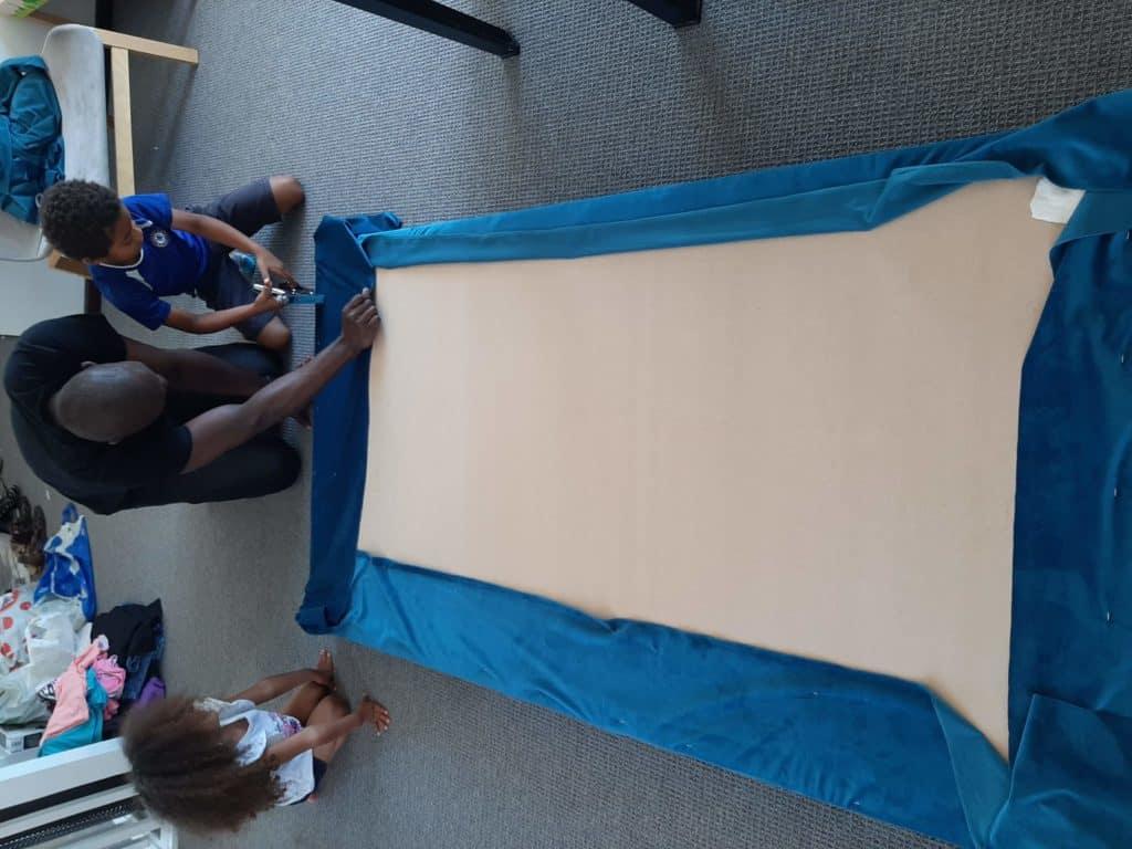 DIY upholstered headboard in progress. Stapling fabric to board.