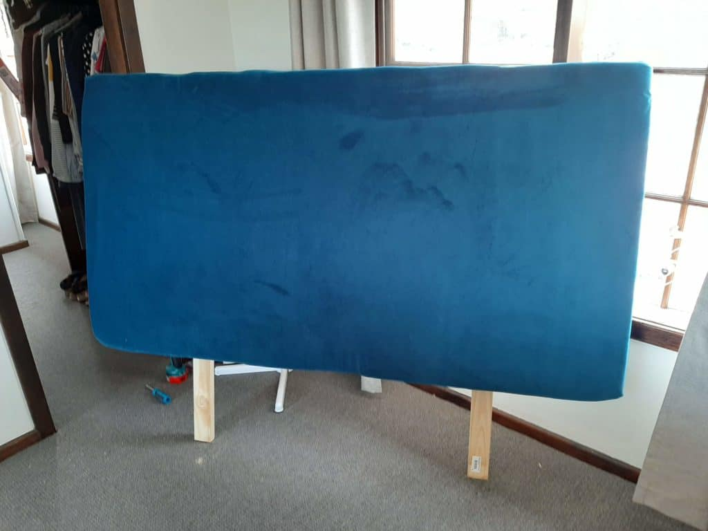 DIY upholstered headboard complete. Standing up on timber supports.