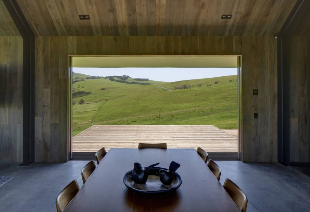 Escarpment House by Atelier Andy Carson Architects. Photo of dining area opening out to views of rolling hills. Timber paneling lines the walls and ceilings
