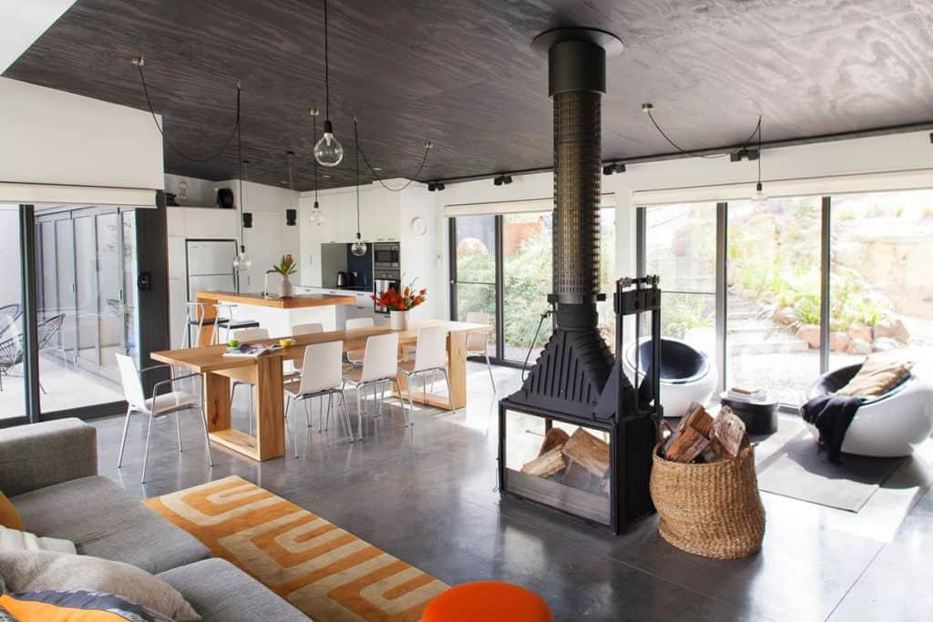 DP Toscano Architects' Daylesford shed house interior living space with wood burner and large amounts of glazing to see the landscape