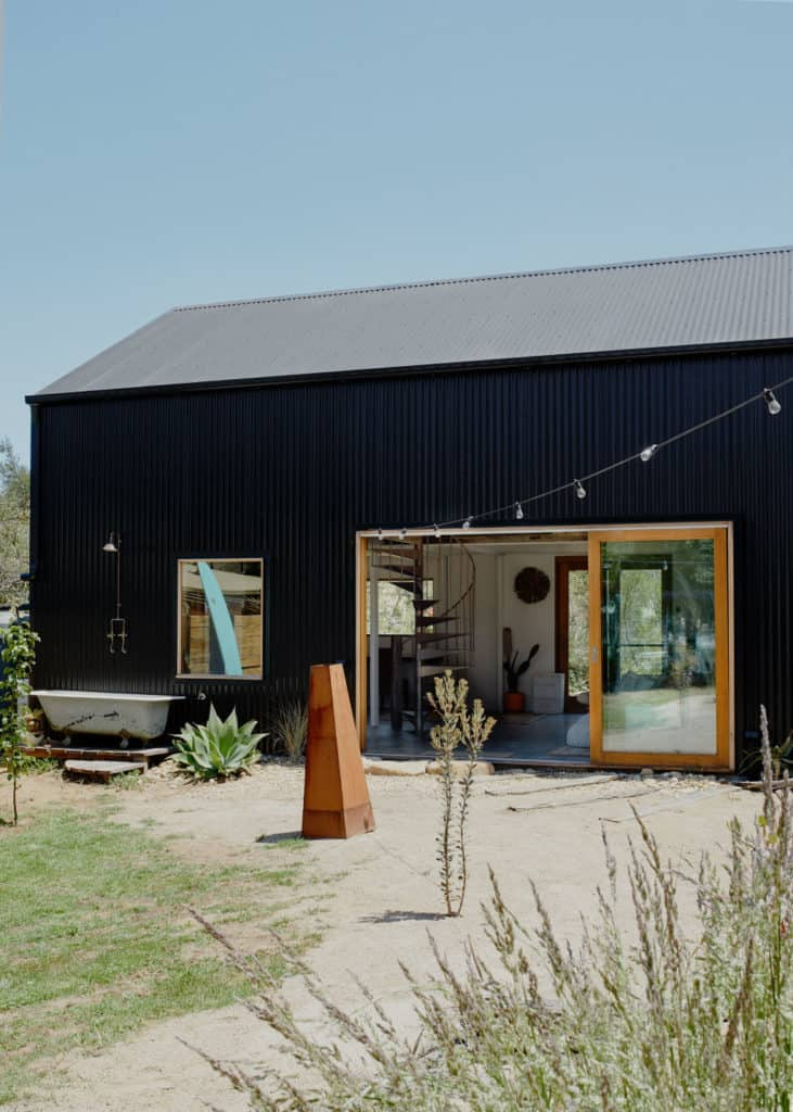 Rhys Uhllich's Shed House. Black colourbond steel cladding and recycled windows and doors