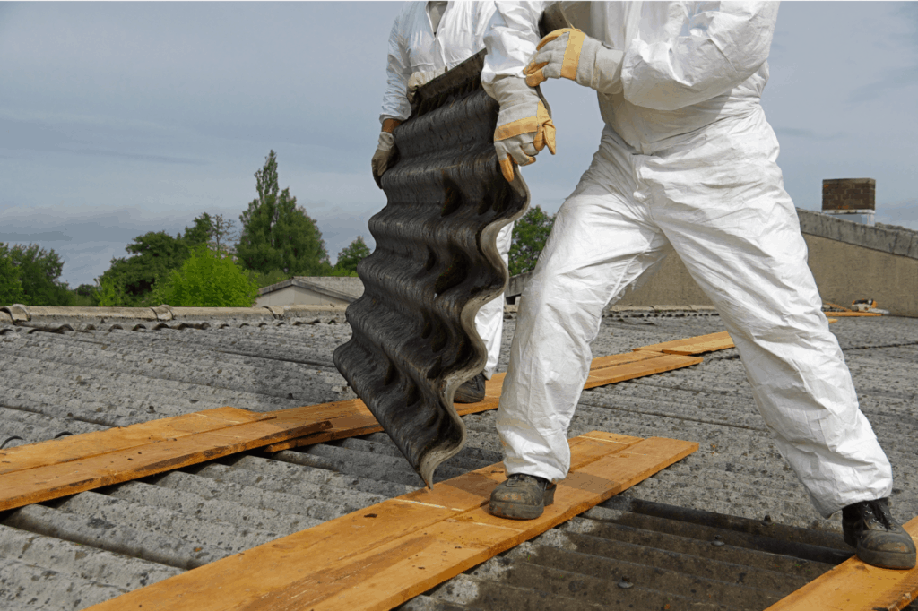A photo of a person removing asbestos roofing sheets for a roof